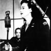 Jane Frohman in uniform facing microphone.