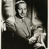 Portrait of Tennessee Williams sitting in chair with hands clasped holding a cigarette holder.