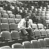 Elia Kazan sitting on top of theatre seats (wide).