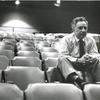 Elia Kazan sitting on top of theatre seats (close-up).