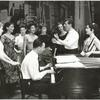 Stephen Sondheim on piano with Leonard Bernstein and Carol Lawrence (on far right) standing amongst female singers rehearsing for the stage production West Side Story.