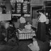A settlement house worker visits a newly-arrived family
