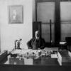 William Williams at his desk [front view].