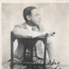 Autographed photo of William Grant Still seated in holding a cigar.