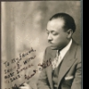 Autographed photo of William Grant Still seated in holding a pipe.