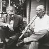 Henry Cowell demonstrating the Japanese shakuhachi to Edgar Varese at the Strongin's home on Long Island
