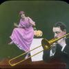 [Man plays trombone, woman dances on table.]