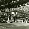 View of West 125th Street and Eighth Avenue showing elevated train along Eighth Avenue, businesses and pedestrians, 1939