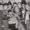 Basil Rathbone (center) surrounded by group of unidentified boys backstage during run of the stage production Sherlock Holmes