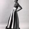 Unidentified model wearing dark Norman Norell evening dress with wide belt, dark top with turtleneck and floor length skirt with fur ruff