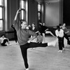 Choreographer Jerome Robbins demonstrating a move while smoking as ballet dancers look on.