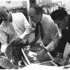 "New York City Ballet rehearsal room, unidentified dancer, Jerome Robbins, George Balanchine and costumer Barbara Karinska looking at Nicholas Benois' sketches for ""Theme and variations"", choreography by George Balanchine (New York)"