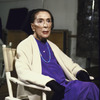Portrait of choreographer Martha Graham sitting in front of mirror in rehearsal room