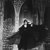 """Actor Raul Julia holding up his cape in a scene from the Broadway production of the play """"Dracula"""""""