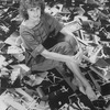 Photographer Martha Swope sitting on a floor covered with prints of her photos