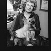 Broadway producer Nell Nugent holding her dog in her office