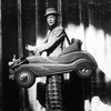 """Actor Gene Nelson doing a vaudeville turn while """"wearing"""" a tiny car in a scene from the Broadway musical """"Follies.""""."""