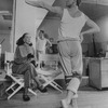Choreographer Martha Graham sitting in chair watching as dancer Mikhail Baryshnikov rehearses before her in her studio.