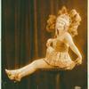 Female dancer sitting on a pillar